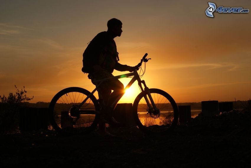 cyklista, západ slnka, silueta chlapa, žltá obloha