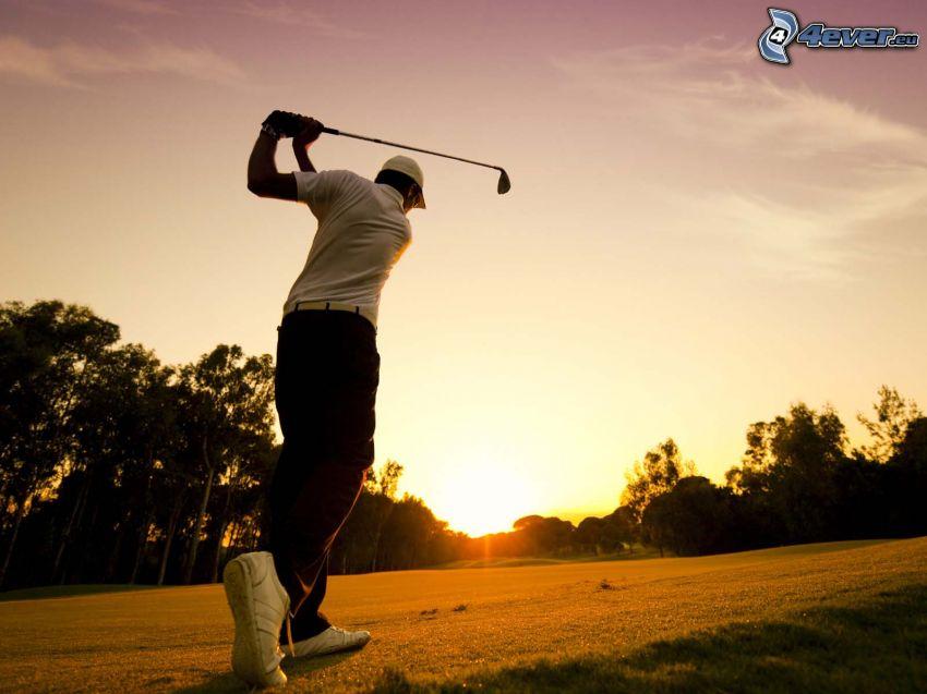 golf, golfista, západ slnka za stromom, siluety stromov
