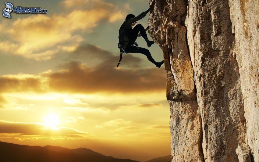 horolezec, skala, západ slnka nad horami, žltá obloha