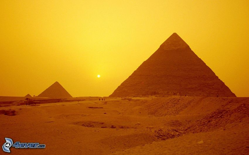 Egyptské pyramídy pri západe slnka, oranžová obloha, slabé slnko