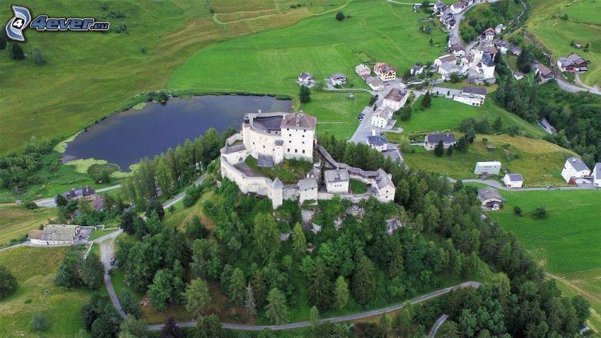 hrad Tarasp, ihličnaté stromy, jazero, lúky, domčeky