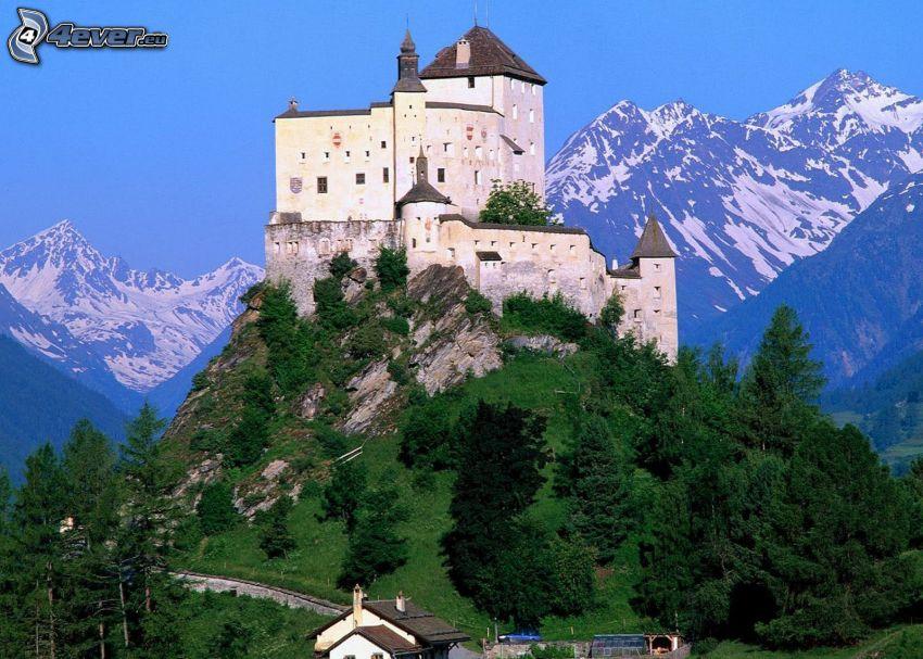 hrad Tarasp, zasnežené hory, ihličnaté stromy