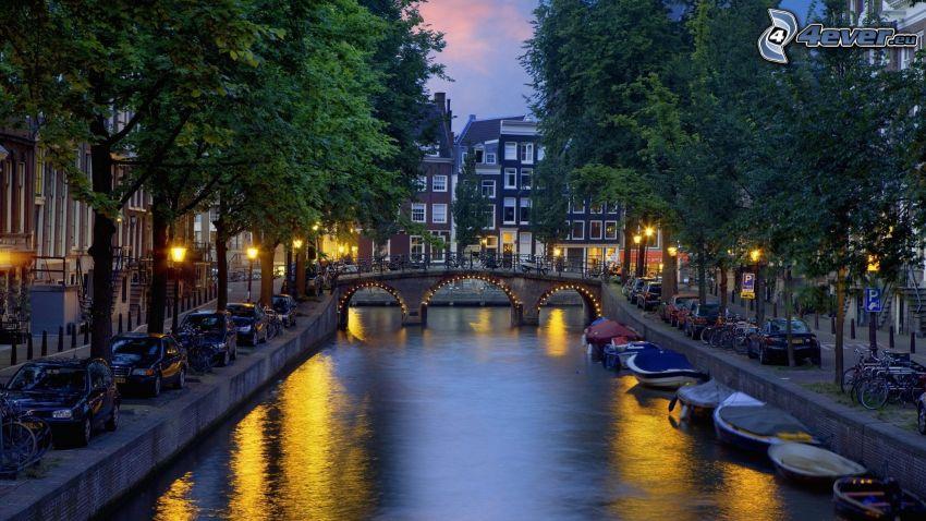Amsterdam, kanál, loďky pri brehu, večerné mesto, osvetlený most
