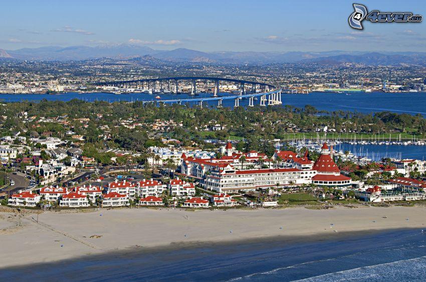 výhľad na mesto, domy, more, piesočná pláž, most