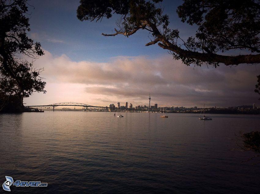 Auckland Harbour Bridge, loďka na mori, večer