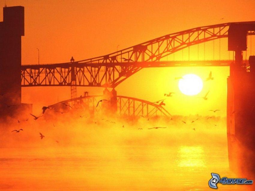 železný most, prízemná hmla, oranžový západ slnka