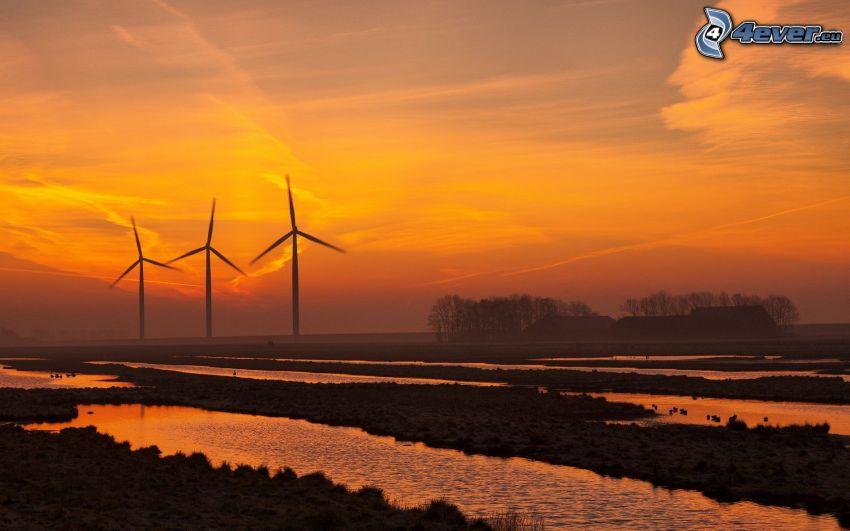 veterné elektrárne pri západe slnka, oranžová obloha, mláky