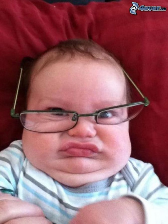 child with glasses, grimacing