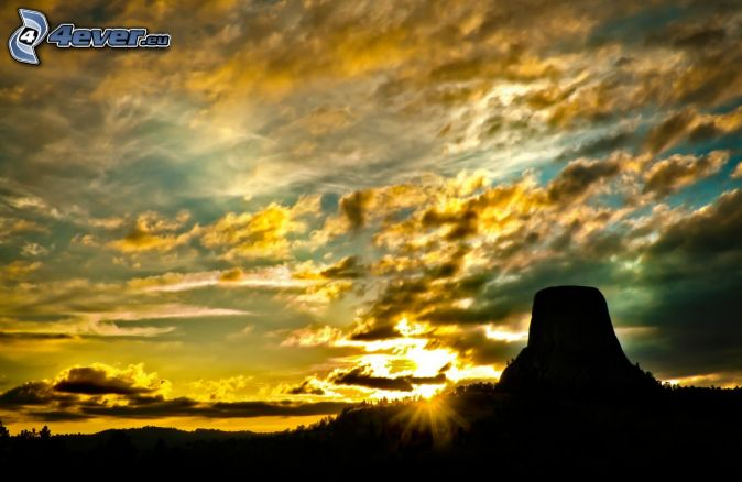Devils Tower, rock, silhouette, sunset, sunbeams, yellow clouds