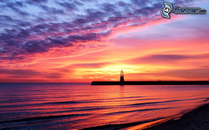 sunset at sea, pink sky, pier with a lighthouse