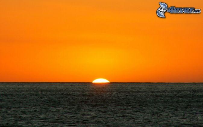 sunset behind the sea, orange sky