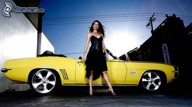 brunette, black dress, yellow car, convertible