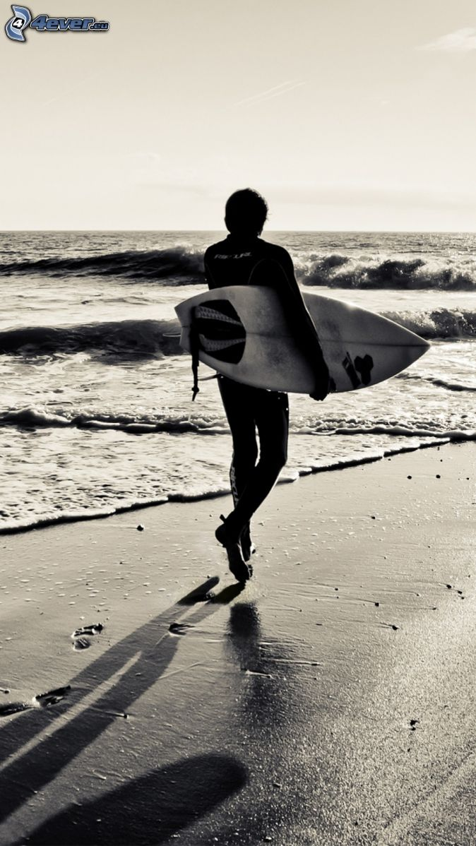 surfer, sandy beach, open sea, footprints in the sand, black and white photo