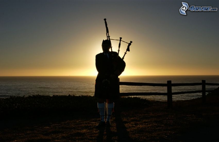 playing the bagpipes, sunset behind the sea