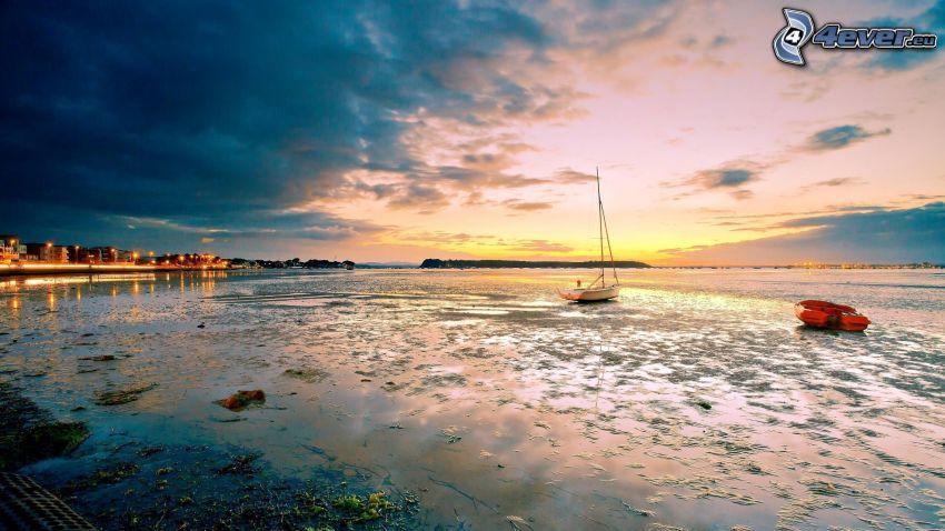 boat at sea, coastal city, evening sky