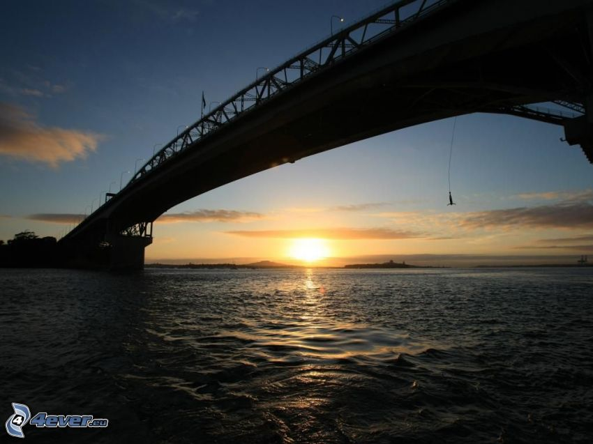 Auckland Harbour Bridge, sunset behind the sea