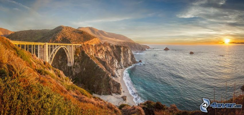 Bixby Bridge, coastal reefs, sunset behind the sea