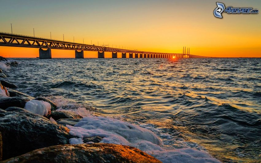 Øresund Bridge, sunset behind the sea, yellow sky