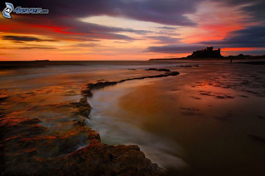 Bamburgh castle, rocky beach, after sunset
