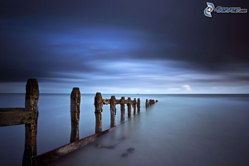 old wooden fence, sea, dark sky