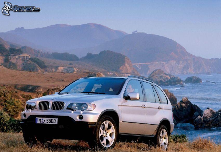 BMW X5, hills, rocks in the sea