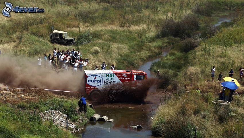 MAN, truck, stream, mud, dust, people, grass