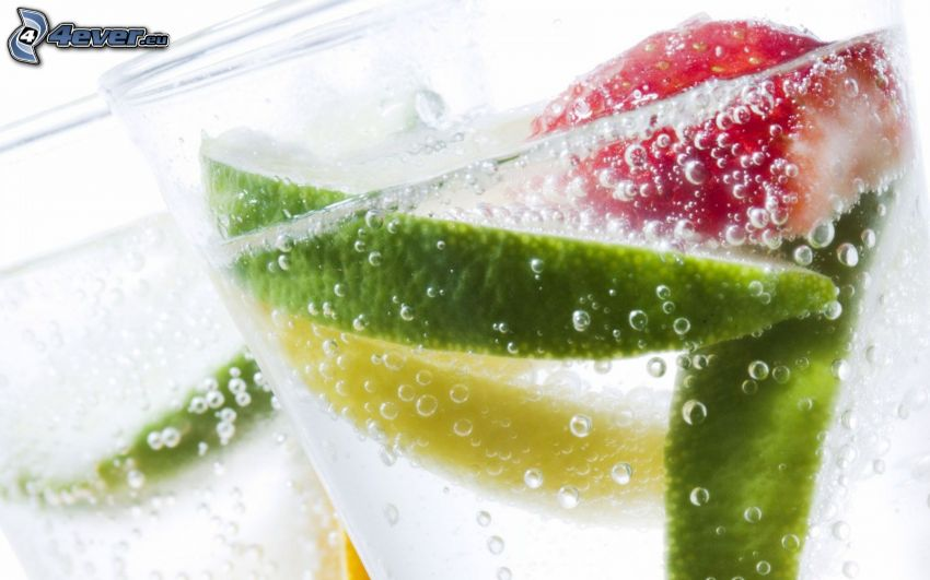 mixed drinks, a slice of lime, strawberry, bubbles