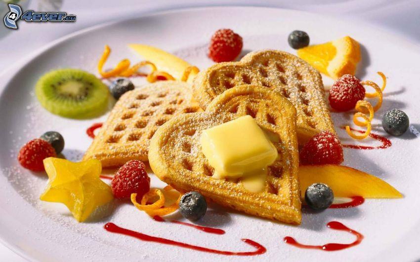 waffles, butter, raspberries, blueberries, orange, kiwi