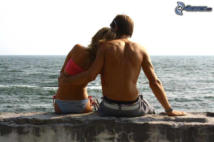 couple on the wall, couple by the sea, hug