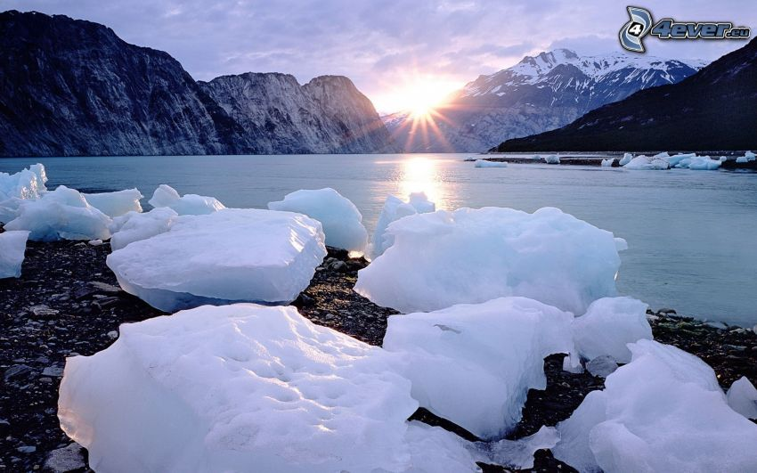 calm winter lake, ice floe, sunset, snowy mountains