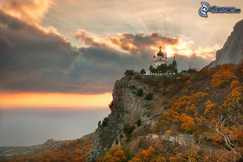castle, rock, sunbeams behind clouds, yellow trees