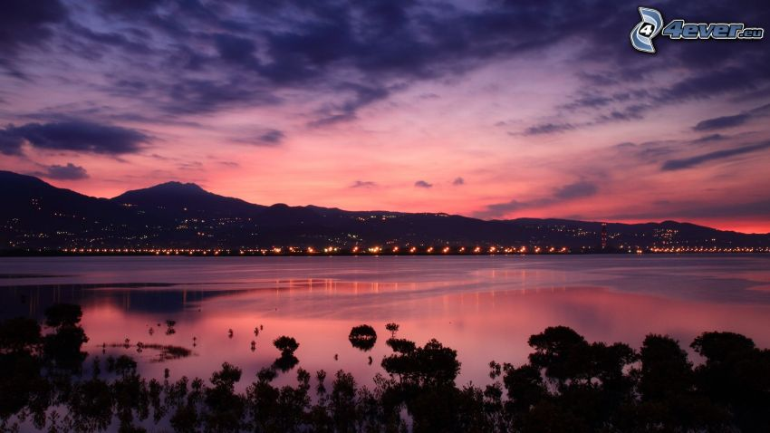 after sunset, large lake, hills, lights, purple sky