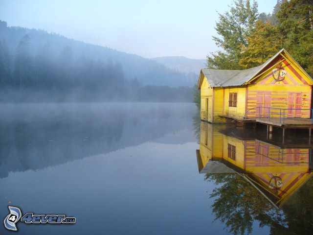 house on water, mountains, forest, mist over the lake