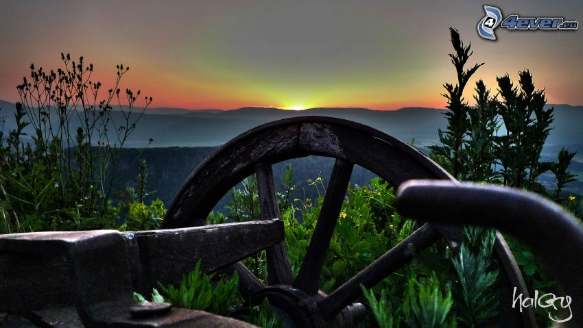 old wooden chariot, sunset behind the mountains, greenery