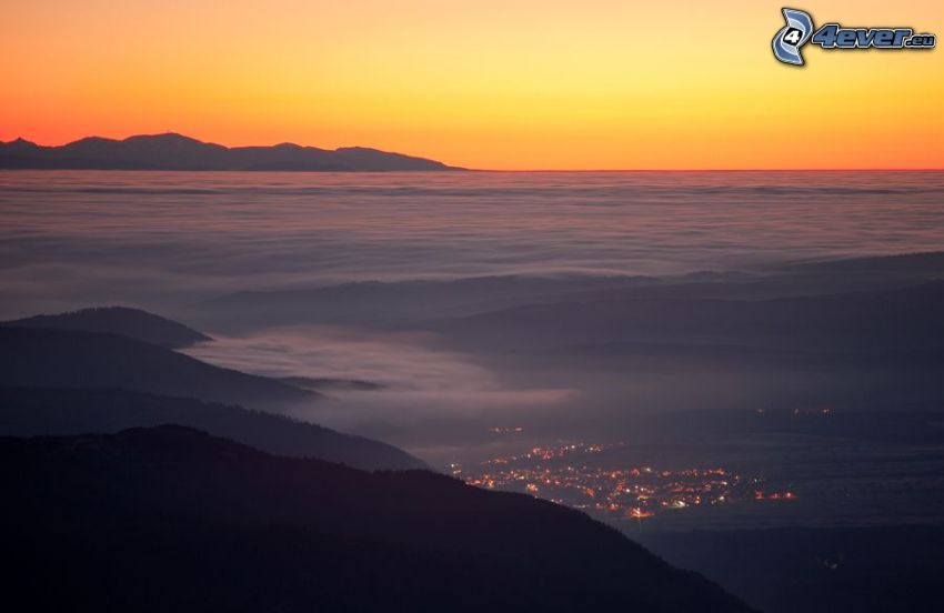 over the clouds, view of the city, hills, after sunset, orange sky, evening
