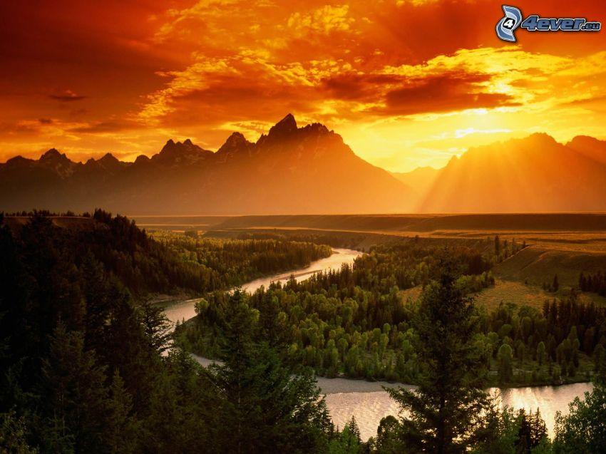 Snake River, Grand Tetons National Park, sunset over mountains, forest, sunbeams