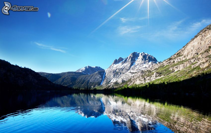 sun over lake, rocky hills, blue sky, reflection