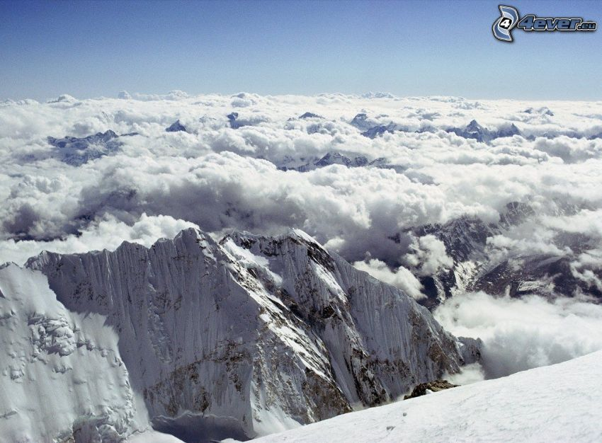 over the clouds, snowy mountains