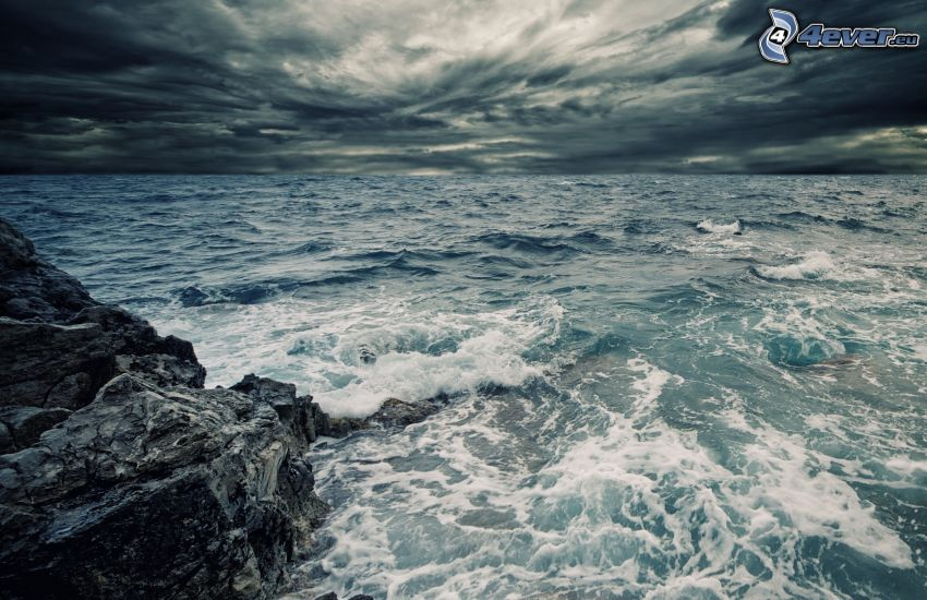 dark clouds over the sea, rocks