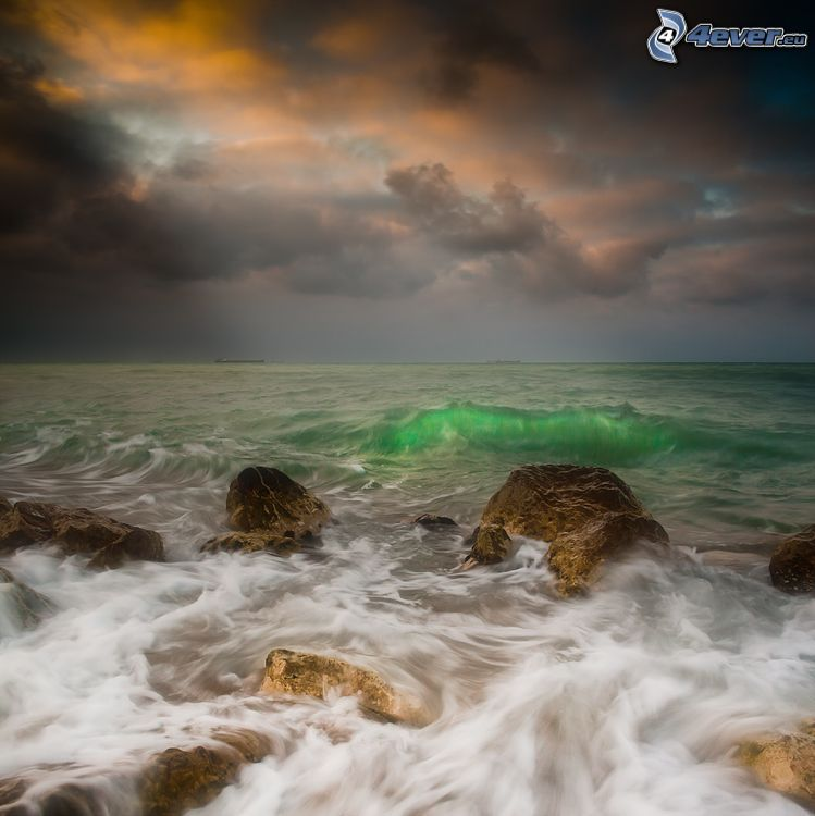 green sea, waves on the shore, rocks in the sea, storm clouds