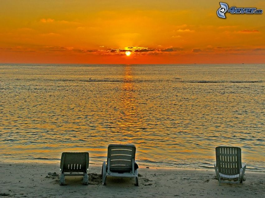 orange sunset over the sea, deck chairs on the beach
