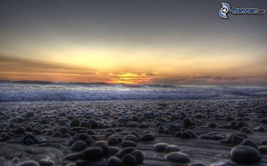 rocky beach, sunset behind the sea