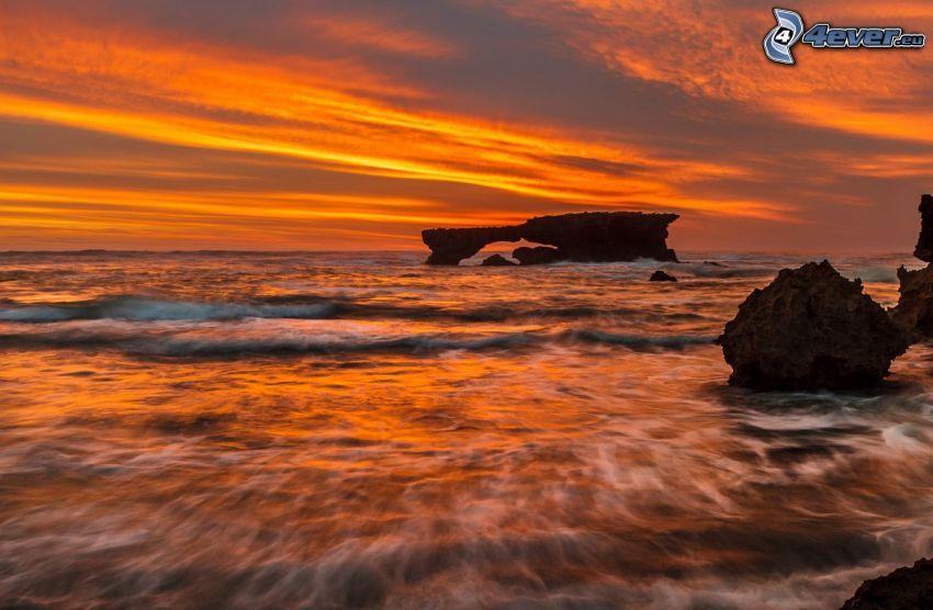 rocky gate on sea, rocks in the sea, orange sunset over the sea