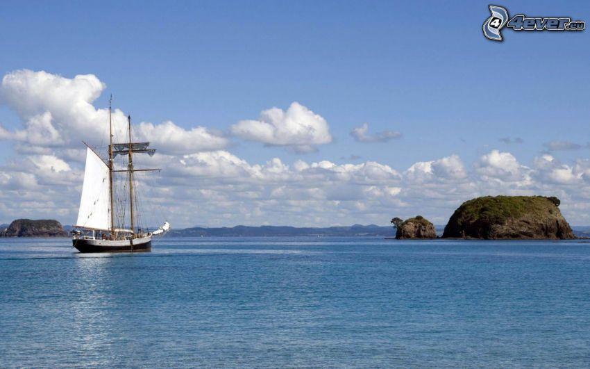 sailing boat, rocks in the sea