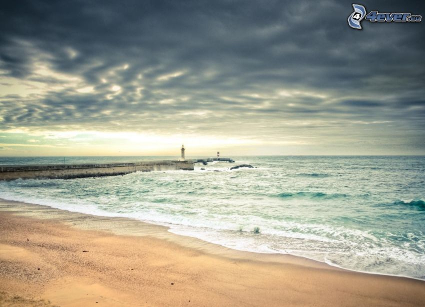 sandy beach, waves on the shore, sea, pier with a lighthouse, clouds
