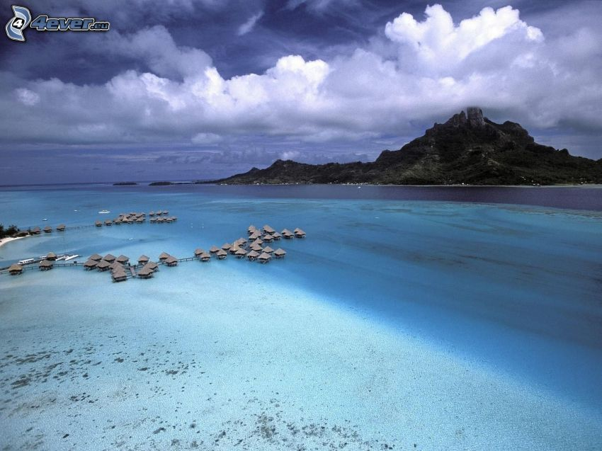 seaside bungalows on Bora Bora, rocky island, clouds