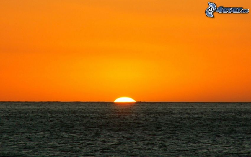 sunset behind the sea, orange sky