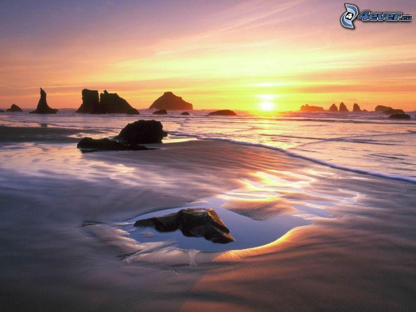 sunset over the beach, rocks, sea