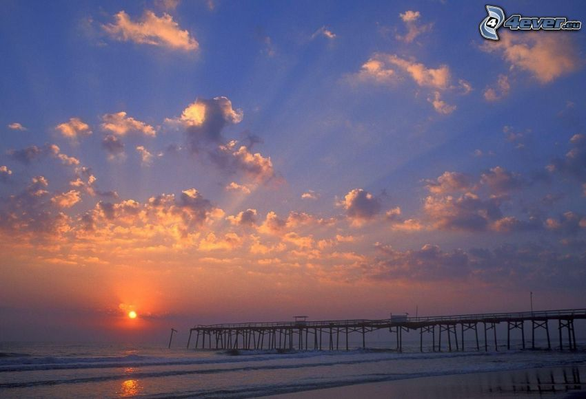 sunset over the sea, long pier, waves, clouds