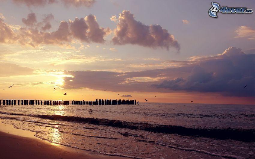 sunset over the sea, pillars, sandy beach, evening sky